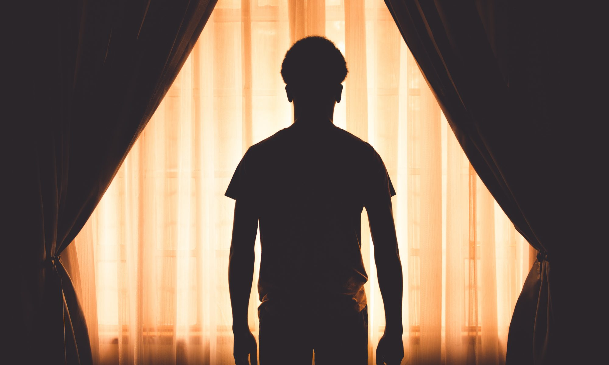 Silhouette of a man, standing in the shadows, desparate to get noticed.