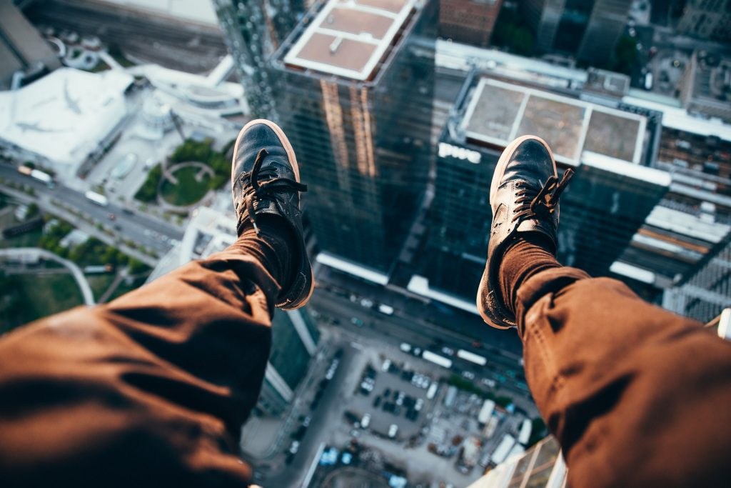 Sitting on top of a building looking down at the world beneath your feet.